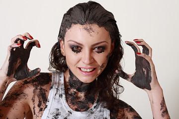 woman with face and body covered in mud