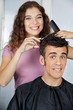 Happy Hairdresser Cutting Client's Hair At Salon