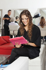 Client Using Tablet With Hairdresser And Women In Salon
