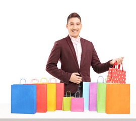 A handsome young man posing with many shopping bags