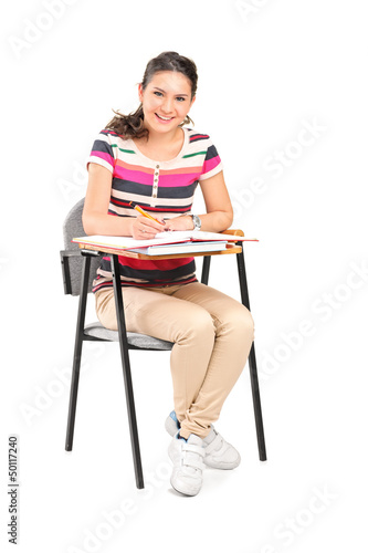 A smiling woman  sitting on a chair and writing down notes