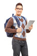 Smiling male student with backpack holding a tablet