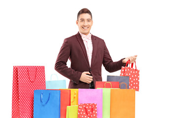 Handsome young man with many shopping bags
