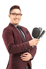 Young male hair stylist holding three hair brushes
