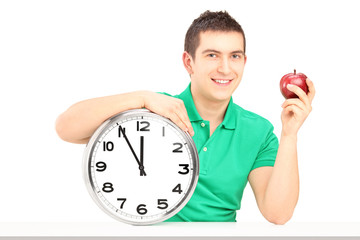 Young man holding wall clock and red apple on a table