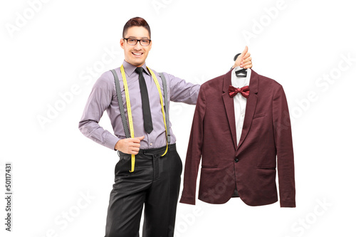 Male fashion designer holding a suit on a hanger