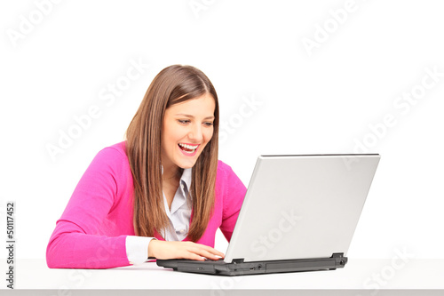 Smiling young female sitting and looking at a laptop