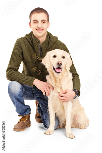 Smiling young man posing with a retriever dog