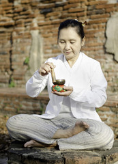 Woman playing a tibetan bowl, traditionally used to aid meditati
