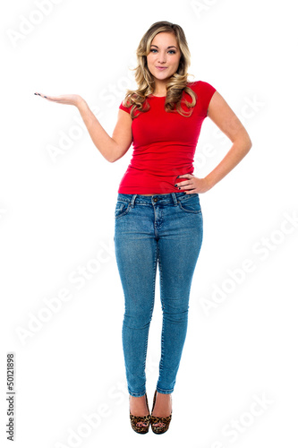 Young girl in trendy wear presenting something