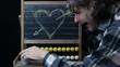 end of love concept, man erasing an heart sketch on chalkboard