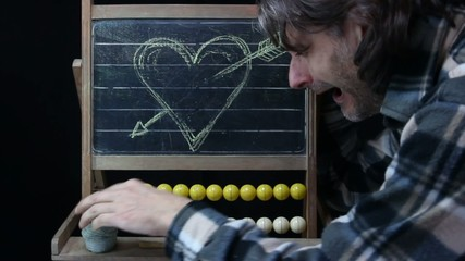end of love concept, man erasing an heart sketch on chalkboard