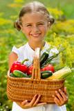 Vegetable garden - lovely girl with basket of vegetables