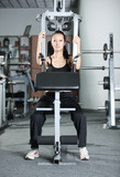 The girl is engaged in gym doing exercise strengthens the chest poster
