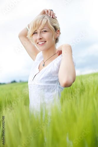 lächelnde junge frau steht im hohen gras