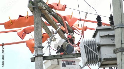 Electricians repairing power transformer.