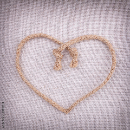 A love heart made of string on fabric vintage background