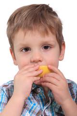 Junge beisst in Zitrone