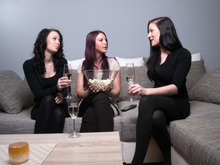 three women speaking on the sofa with popcorn and champagne