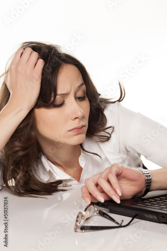 secretary with a laptop looking at his watch in boredom on white
