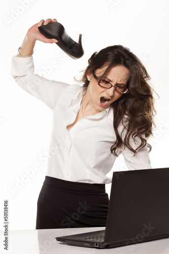 nervous and angry business woman destroys her laptop with high h