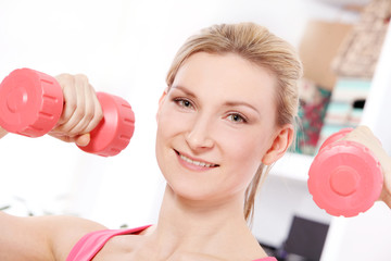 Young beautiful woman with dumbbells