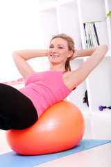 Young woman working out with fitball