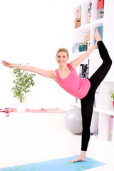 Young beautiful woman stretching at home