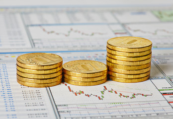 Financial settlement with the charts and golden coins. Selective