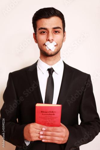 Mann mit Pflaster auf Mund und Gesetzbuch