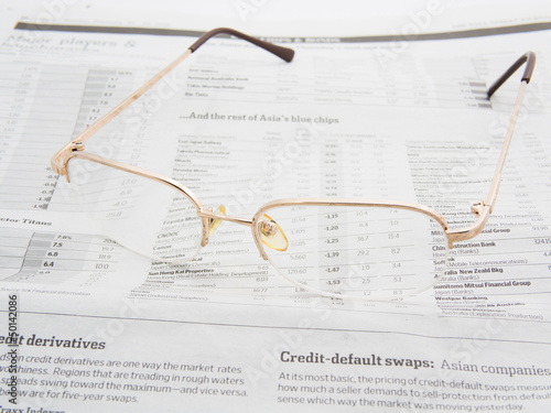 Glasses on the stock market index page of a newspaper