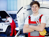 Fototapety Apprentices for car mechanic is satisfied with his job