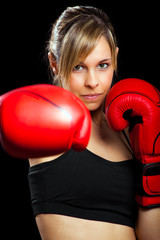 Young woman wearing boxing gloves isolated on black