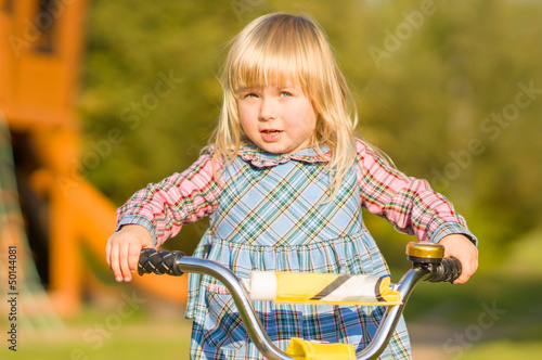 Adorable girl ride on bike with training wheels on playground in