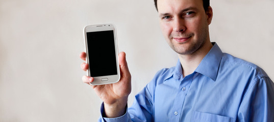 young man shows smart phone in the right hand
