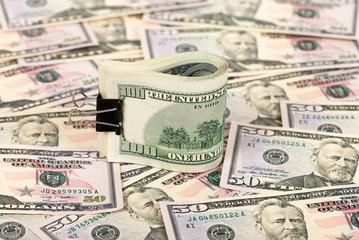 Folded hundred dollar bill on money background