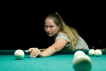 Woman aiming for billiard table