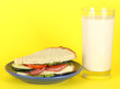 Sandwich on plate with milk on yellow background