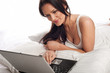 Smiling woman using a laptop in bed