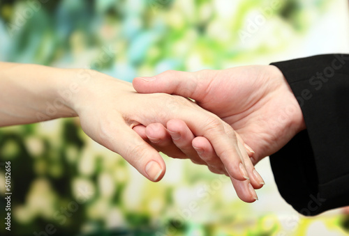 Priest holding woman hand, on green background