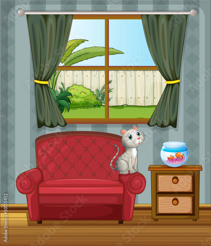 A cat at the sofa watching the fish in the aquarium