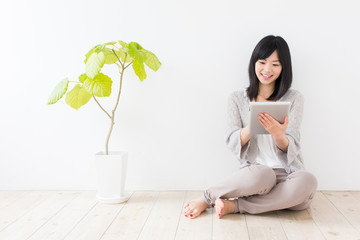 attractive asian woman using tablet in the room