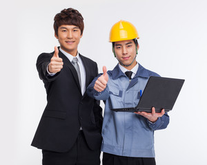Business man and engineer looking laptop.
