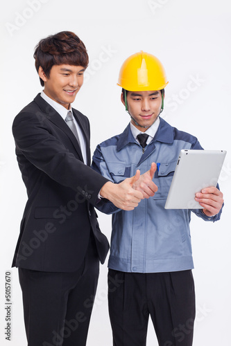Asian business man and engineer have a pad PC.