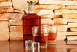 Bottle and Glasses of whiskey and ice on brick wall background