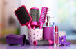 Hair brushes, hairdryer and cosmetic bottles in beauty salon.