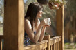 Cute girl seeing how the sun rises from a log cabin's deck - 50161478