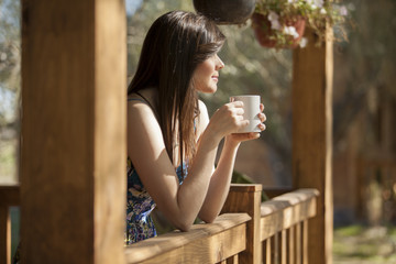 Cute girl seeing how the sun rises from a log cabin's deck