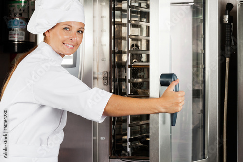 Female Chef Opening Oven Door