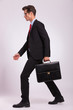 man holding briefcase & walking